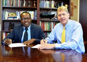 Joshua Paul of Build and Bridge, left, and Southern Wesleyan University President Todd Voss, sign a Memorandum of Understanding for a collaboration that will help build sustainable communities in economically strapped areas of Haiti by supporting entrepreneurship in business, fishing technology and agro technology.