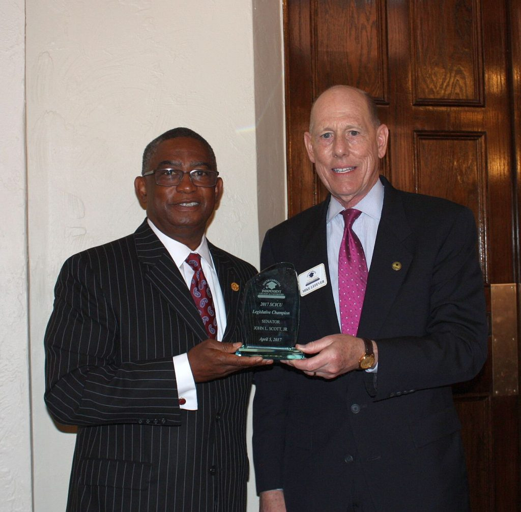 Sen. John L. Scott, Jr. (L) is presented with the SCICU 2017 Legislative Champion Award by SCICU President Mike LeFever (R).